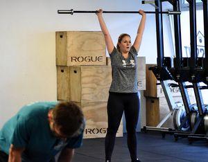 Junge Frau beim Training mit leerer Langhantel gestreckt über Kopf