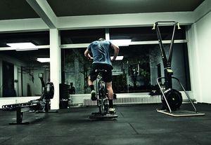 Rückenansicht eines Athleten beim Workout auf dem Airbike