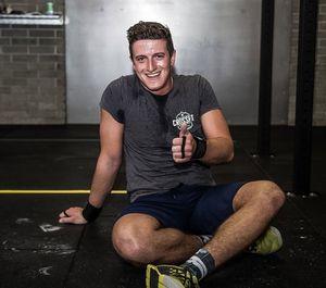 Junger Mann sitzt verschwitzt am Boden und grinst glücklich in die Kamera nach seinem WOD