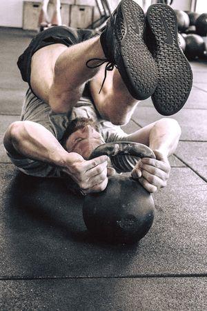 Aufnahme eines Mannes beim Workout mit Toes to Kettlebell