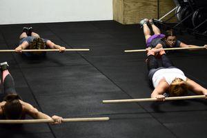 Frauen auf dem Boden liegend mit dem Bauch nach unten beim Trainieren des Superman Holds