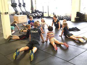 Coach Raphael und seine Kids beim Dehnen während des Trainings