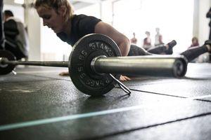 Detailaufnahme Langhantel mit Gewicht, im Hintergrund macht eine junge Frau einen Burpee