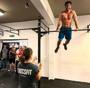 Athlet grinst strahlend in die Kamera während er sich beim Bar Muscle Up auf der Stange hält