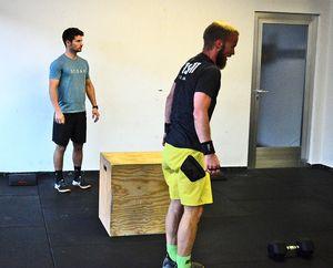 Athleten beim Workout, einer hat Pause, einer arbeitet mit den Dumbells