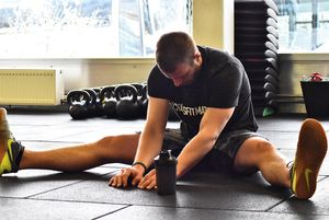 Junger Mann beim Stretching nach dem Workout, breitbeinig sitzend am Boden