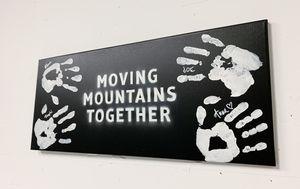 Detailaufnahme des selbstgemachten Bildes mit den Handabdrücken der Coaches und dem Slogan Moving Mountains Together