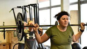 Junge Frauen beim Gewichtheben mit der Langhantel im Genick