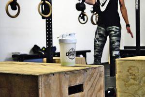 Detailaufnahme Trinkbecher mit Crossfit Zillertal Logo auf Holzbox, dahinter Athletin beim Workout