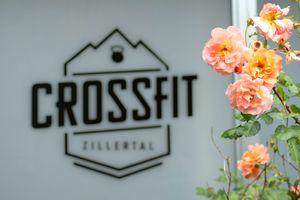 Detailaufnahme Logo Crossfit Zillertal mit Blumen im Vordergrund © Crossfit Zillertal
