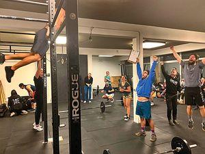 Athlet schafft seinen ersten Bar Muscle Up und der Raum voller Member tobt und freut sich mit ihm
