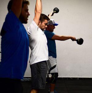Profilaufnahme von vier Athleten, die die Kettlebell in unterschiedlichen Positionen schwingen