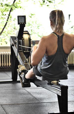 Rückenansicht einer Athletin beim Rudern auf dem Concept-Rudergerät