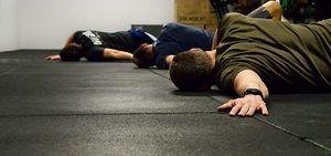 Detailaufnahme von Crossfit Mitgliedern, die am Boden liegend ihre Schultern ausdehnen
