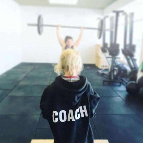 Rückenansicht eines kleinen Mädchens im Oversize-Pullover, auf dem in großen Buchstaben Coach geschrieben steht
