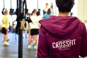 Junge Frau von hinten mit Crossfit Zillertal Logo auf dem Rücken der Jacke, im Hintergrund Trainingsgruppe beim Workout